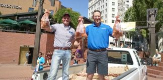Oregon State Rep. Greg Smith, left, and Hermiston Mayor Drotzmann hand out free Hermiston potatoes at Pioneer Courthouse Square in Portland Saturday.
