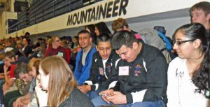 Isaac Murguria checks for text messages just prior to the relay competition. To his immediate right is Armando Mendoza and to his far right is Carlos Fonseca. To his left is Ana Mendoza.